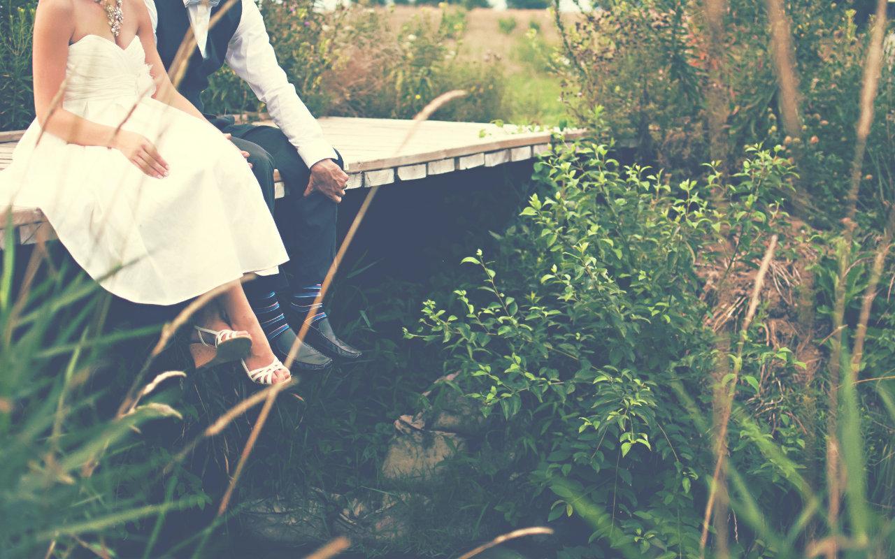 Ein Hochzeitspaar sitzt an einem See auf einem Steg